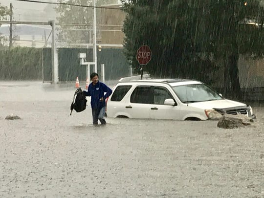 Manny Leveigh walks away from his car stuck in rising water on Nepperhan Avenue in Elmsford.