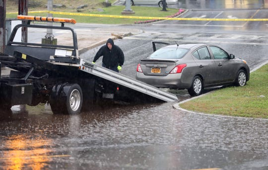 Andrew Spellman from AVS Towing in Yonkers, prepares to put a car on a flatbed truck after it got caught in rising waters in the Kohl's parking lot in Yonkers, Sept. 25, 2018.
