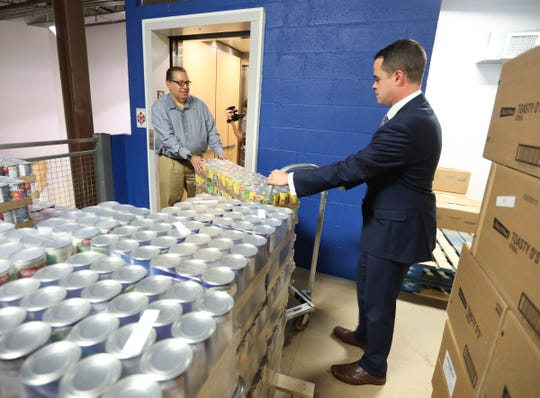 Jim Burton, director of operations for People to People, left, and Senator David Carlucci move several cases of peaches from the new elevator on to the new storage mezzanine at the People to People headquarters in Nanuet on Tuesday, September 25, 2018.