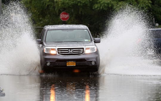 A vehicle drives across a flooded section of Waverly Ave in Mamaroneck during a heavy rainfall  Sept. 25, 2018.