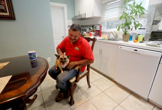 Antonio Reyes of Port Chester sits with his dog Freddie after returning home from his job as a landscaper Sept. 6, 2018.  Reyes, who has lived in Port Chester after immigrating from El Salvador in the early 1980's, became a U.S. citizen this past January. He said that the first thing he did after becoming a citizen was to register to vote.