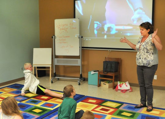 Susan Cooper, head of Youth Services at the Wichita Falls Public Library, uses YouTube videos Monday to help demonstrate how to safely yo-yo during her All Things String class.