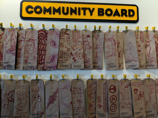 Many paper bags customers had drawn on where hung next to the soda fountian.