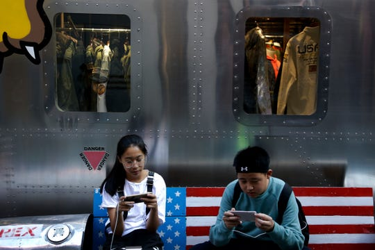 Shoppers sit on a bench with a decorated with U.S. flag browsing their smartphones outside a fashion boutique selling U.S. brand clothing at the capital city's popular shopping mall in Beijing, Monday, Sept. 24, 2018. China raised tariffs Monday on thousands of U.S. goods in an escalation of its fight with President Donald Trump over technology policy and accused Washington of bullying Beijing and damaging the global economy.
