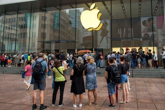 In this Friday, Sept. 21, 2018, photo, foreign tourists watch people queue in line to enter the Apple Store for the debut of the latest iPhones in Shanghai. China imposed new tariff hikes on U.S. goods on Monday, Sept. 24, 2018, and accused Washington of bullying, giving no sign of compromise in an intensifying battle over technology that is weighing on global economic growth.