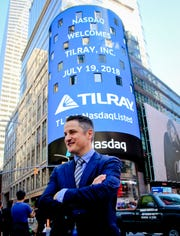 FILE- In this July 19, 2018, file photo Brendan Kennedy, CEO and founder of British Columbia-based Tilray Inc., a major Canadian marijuana grower, poses outside the Nasdaq in New York. Investors are craving marijuana stocks as Canada prepares to legalize pot next month, leading to giant gains for Canada-based companies listed on U.S. exchanges. (AP Photo/Bebeto Matthews, File) ORG XMIT: NYBZ464