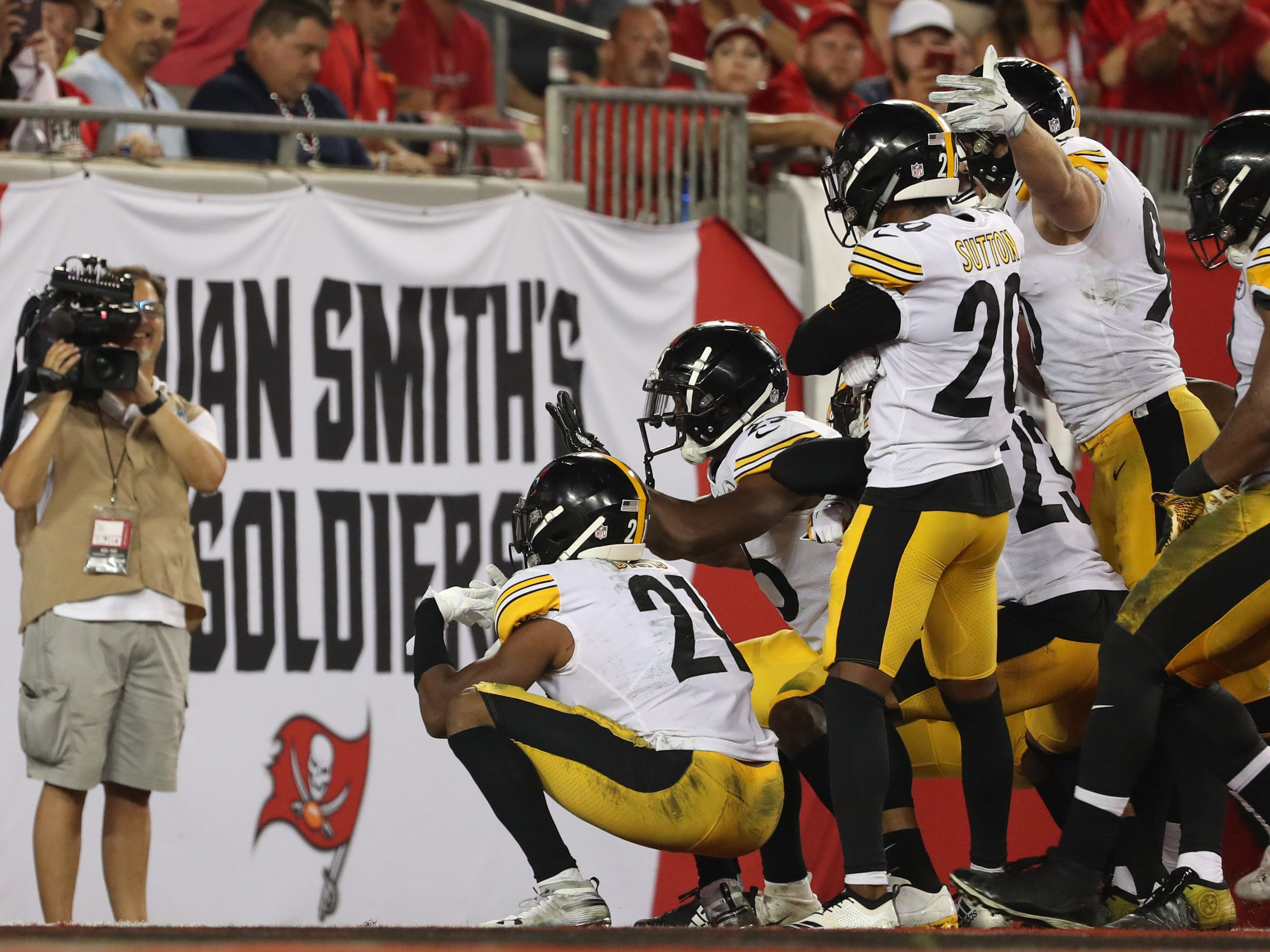 Pittsburgh Steelers players celebrate in the end zone after recovering a fumble against the Tampa Bay Buccaneers.
