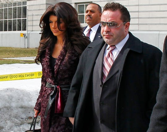 """Teresa, left, and Joe Giudice, from """"The Real Housewives of New Jersey,"""" leave federal court in Newark on March 4, 2014. They each pleaded guilty to bankruptcy fraud, conspiracy to commit mail fraud and wire fraud, and failing to pay taxes."""
