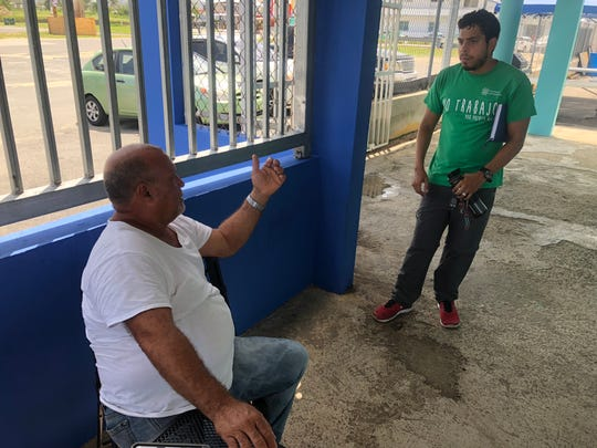Antonio Torres, left, head of the fishermen's association in Punta Santiago, Puerto Rico, talks with Carlos Ayala, a volunteer with the nonprofit Foundation for Puerto Rico. Torres says recovery in Punta Santiago has come mostly at the hands of volunteers like Ayala.