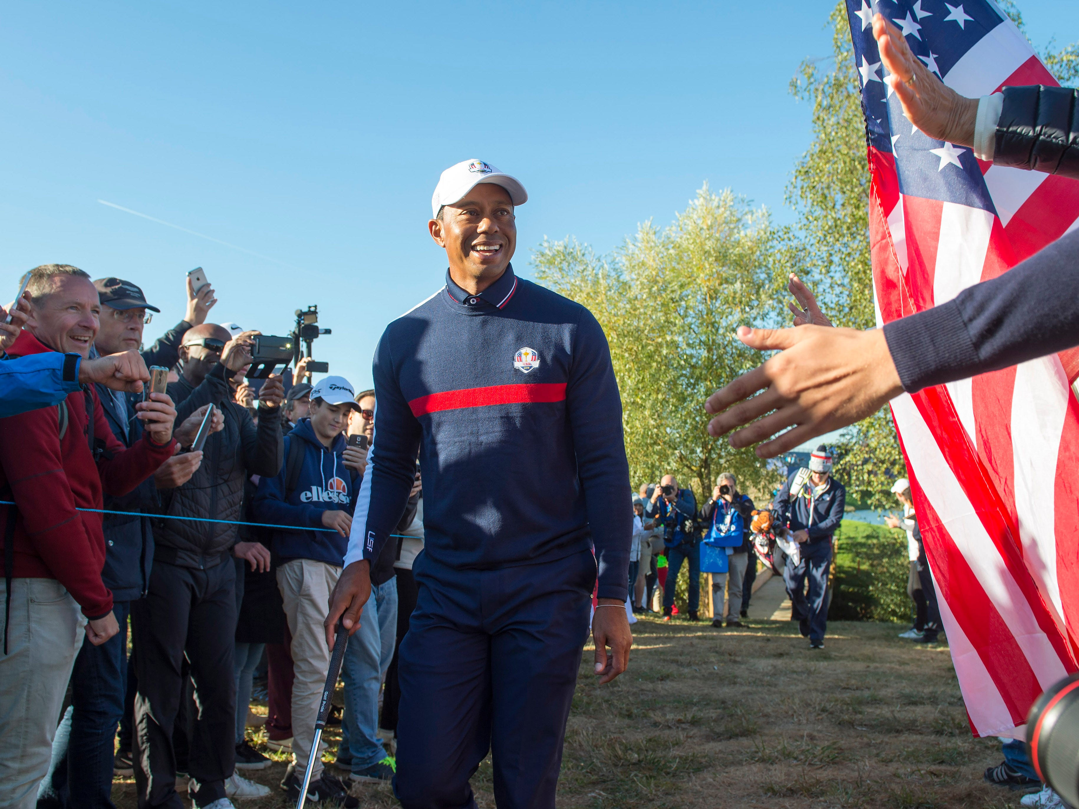 Tiger Woods smiles as he is cheered by spectators during a Ryder Cup practice round.