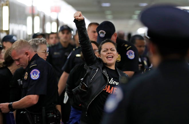 A protester reacts as she is arrested by Capitol Hill Police during a protest against Judge Brett Kavanaugh outside the office of Sen. Susan Collins, R-Maine, on Sept. 24, 2018.