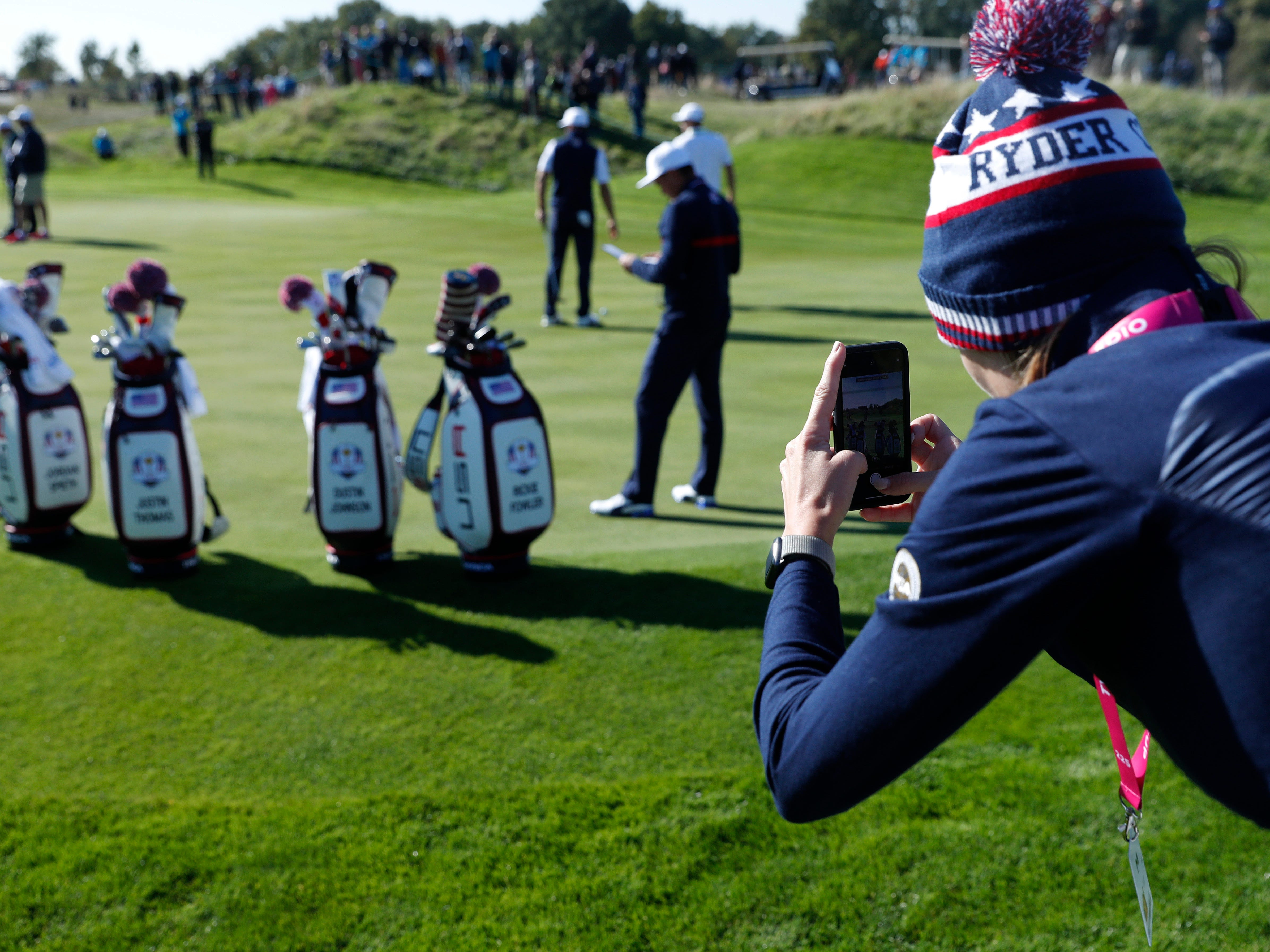 A woman takes photos of golf bags of the US Ryder Cup team.