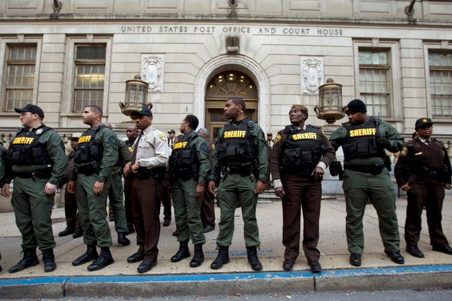 In this Dec. 16, 2015, file photo, deputies stand guard in front of the courthouse main entrance as demonstrators protest outside of the building after a mistrial of Officer William Porter, one of six Baltimore city police officers charged in connection to the death of Freddie Gray, in Baltimore. New crime statistics released Monday, Sept. 24, 2018, by the FBI place Baltimore's homicide rate in 2017 well above that of any other large American metropolis, making it an anomaly in the national crime landscape for U.S. cities with populations over 500,000 people.