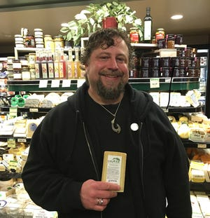 """LeGrand holding Alpine cheese from his Swiss """"adoptee.""""  Photo by Caroline Hostettler"""
