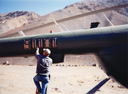 A flight crew member is seen adding the call number 91101 to the tail of a CIA Mi17 helicopter in the Panjshir Valley, Afghanistan in 2001.