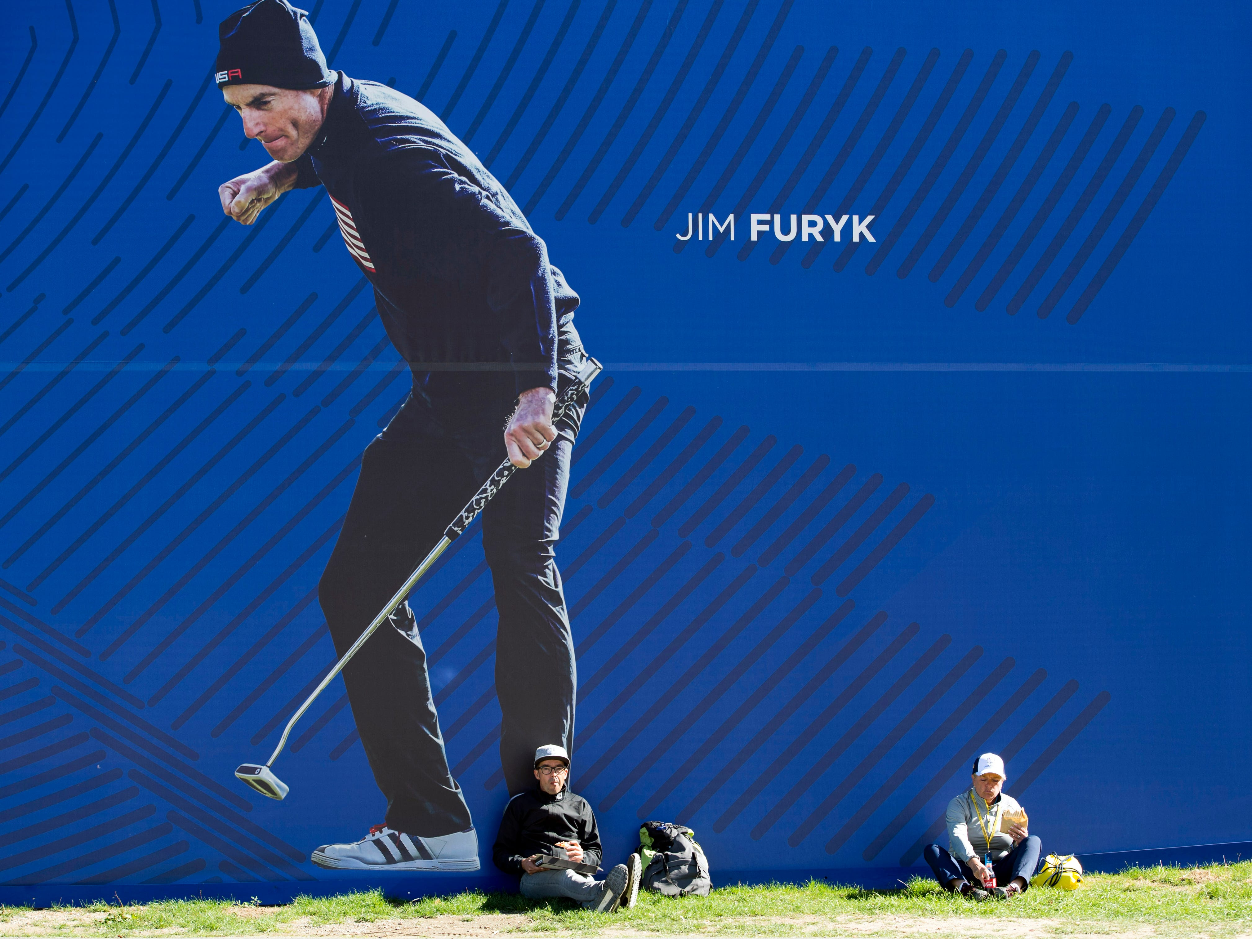 Spectators enjoy a snack under a giant poster of USA Ryder Cup captain Jim Furyk during a Ryder Cup practice round.