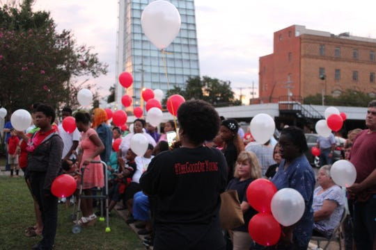 People hold balloons Tuesday evening at the 3rd annual National Day of Remembrance for Murder Victims vigil in downtown Alexandria.