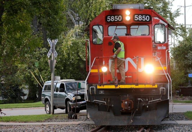 A Canadian National employee inspects the train at the scene of a collision between a truck and the train on Wednesday in Menasha.
