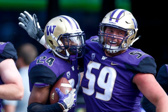 Huskies running back Kamari Pleasant (24) celebrates his 23-yard touchdown run against the North Dakota with offensive lineman Henry Roberts (59).