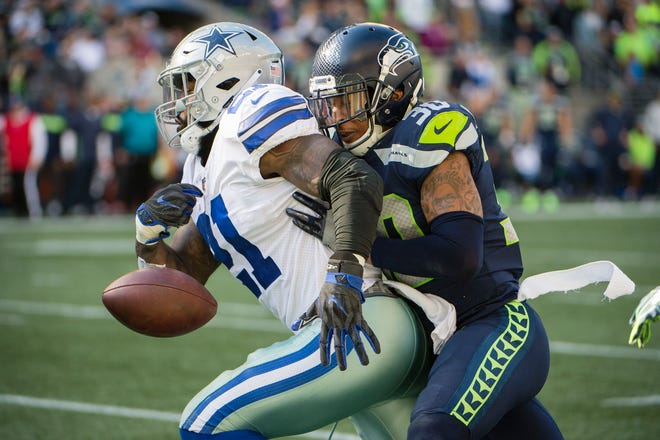 Seahawks safety Bradley McDougald punches the ball away from Cowboys running back Ezekiel Elliott during the second half of Seattle's 24-13 win Sunday at CenturyLink Field. McDougald also has two interceptions on the year.