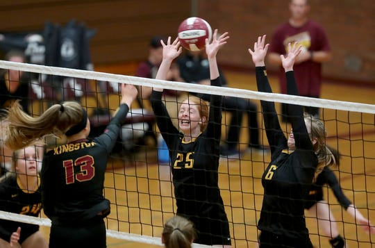 Kingston's Morgan Halady spikes over Faith Smith and Anna Fall of South Kitsap on Sept. 5.