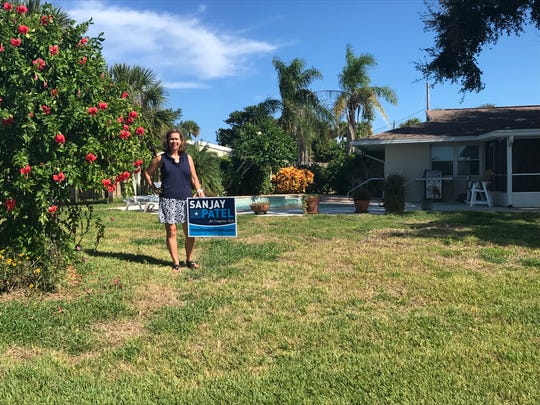 "Sanjay Patel supporter Robin Brothers Heagy stands next to her ""dumpy home,"" a term she uses sarcastically after U.S. Rep. Bill Posey said supporters who display campaign signs of his opponent, Patel, have ""the dumpiest damn house in the neighborhood."""