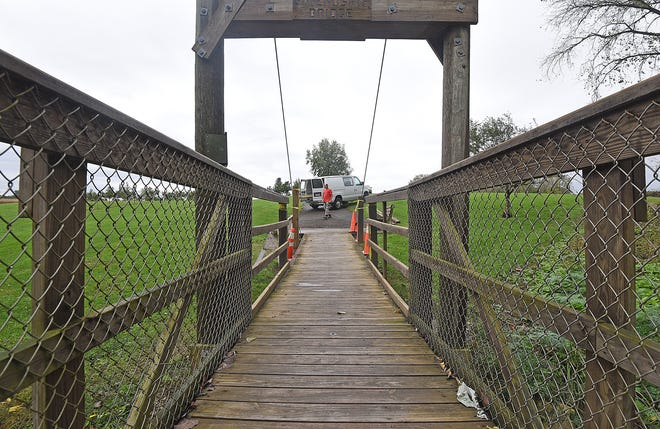Workers arrive Wednesday morning to repair the Bridge of Friendship at the south side of Aumiller Park.