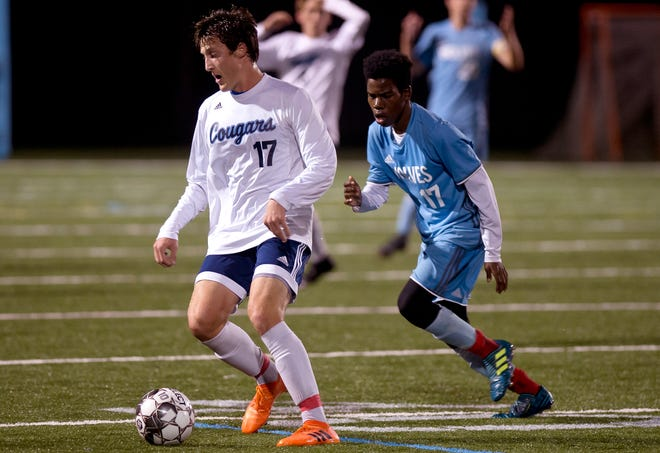 Mount Mansfield's Jack Hayden, left, turns on South Burlington's Abdi Hassan during Tuesday night's high school boys soccer game in South Burlington.