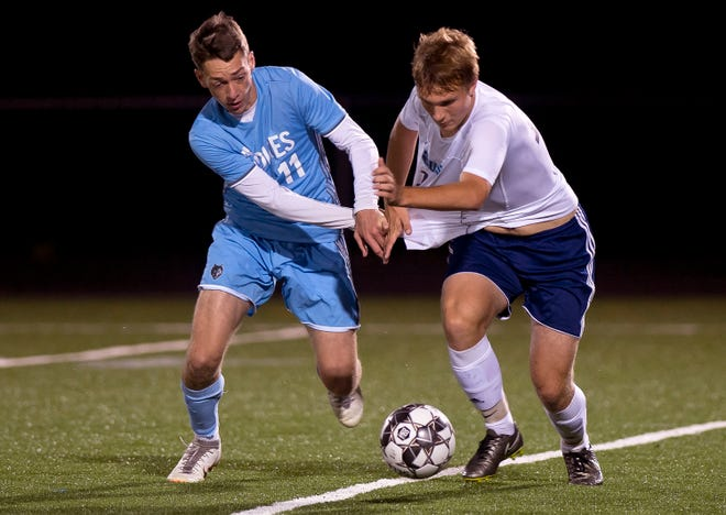 South Burlington's Nolan Antonicci, left, and Mount Mansfield's Quinn Bisbee grapple for control of a loose ball during Tuesday night's high school boys soccer game in South Burlington.