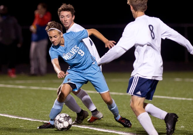 South Burlington's Ben Mazza-Bergeron (9) looks to dribble past two Mount Mansfield defenders during Tuesday night's high school boys soccer game in South Burlington.