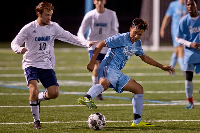 South Burlington's Hari Karki, right, controls a ball ahead of Mount Mansfield's Bobby Merena during Tuesday night's high school boys soccer game in South Burlington.