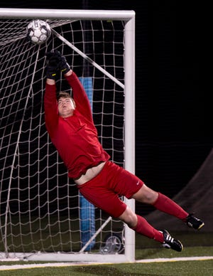 Mount Mansfield goalie Jake Underwood punches a save over the crossbar during Tuesday night's high school boys soccer game in South Burlington.
