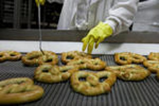 A J&J Snack Foods employee tests the quality of freshly baked pretzels at the company's Pennsauken headquarters at 6000 Central Highway.