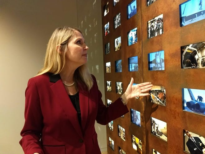 Columbus Downtown Development Corporation and Capitol South Community Urban Redevelopment Corporation Chief Operating Officer Amy Edwards Taylor shows a wall at the National Veterans Memorial and Museum displaying video stories of the jobs people do at the USS George HW Bush Aircraft Carrier.