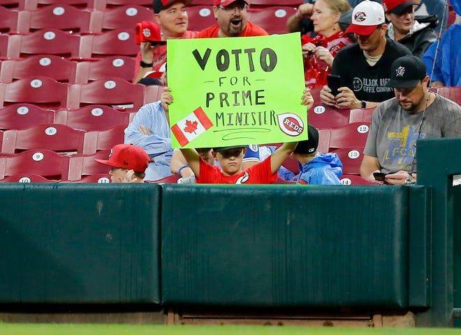 "A young fan lift a sign reading ""Votto for Prime Minister"" with a Canadian flag during the first inning of the MLB Interleague game between the Cincinnati Reds and the Kansas City Royals at Great American Ball Park in downtown Cincinnati on Tuesday, Sept. 25, 2018."