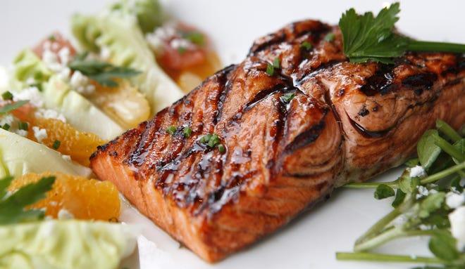 Palomino's Wild-Caught Salmon with Strawberry Balsamic Glaze featuring bibb lettuce, watercress shoots, fresh citrus, feta, and white balsamic dressing.