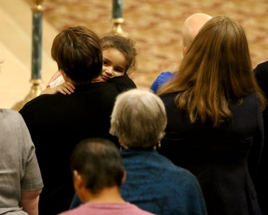 Daniella Ruby, 5, holds tight to her mother Maribel Trujillo-Diaz, during a `Welcome Home' prayer service at St. Julie Billiart Parish, in Hamilton, Tuesday, September 25, 2018. Truijilo-Diaz, an asylum seeker, has been reunited with her family following 17 months of separation.