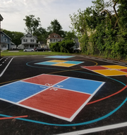 """A walking track, colored Four Square game areas, and random lines meandering in bright yellows, reds, and blues to encourage creative play are among the features of a new """"Oasis"""" area at McKinley Elementary School."""