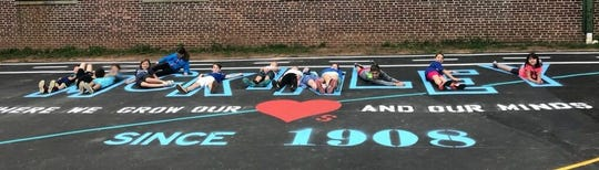McKinley then-3rd graders align themselves last spring with newly painted lettering on the blacktop of the elementary school's new Oasis.
