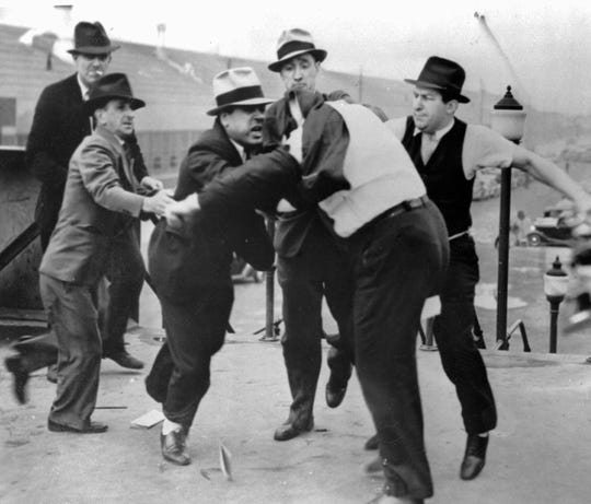 Richard Frankensteen, United Auto Workers organizational director, with coat pulled over his head, is pummeled by Ford Motor. Co. agents at the gate of the Ford River Rouge Complex in Dearborn on May 26, 1937. Ford security personnel were countering the UAW efforts to organize employees at the factory complex.