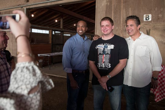 Tyler Hammock of Brighton, center, poses for a photo with Republican senate candidate John James, left, and congressman Mike Bishop during a private fundraiser event for Bishop in Hartland, Friday, September 21, 2018.