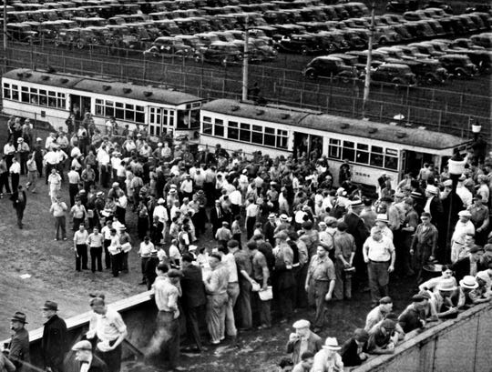"""From this overpass, where fighting occurred between Ford Motor company employees and UAW who were attempting to distribute literature, Ford workers changing shifts Aug. 11, 1937, at the River Rouge plant in Dearborn, watch unionists pass out a """"Ford"""" edition of their paper. Few accepted it. There was no violence."""