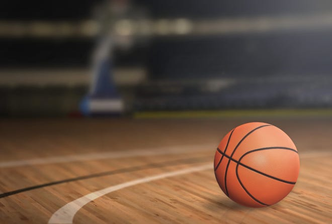 A close up of a basketball on a court floor.