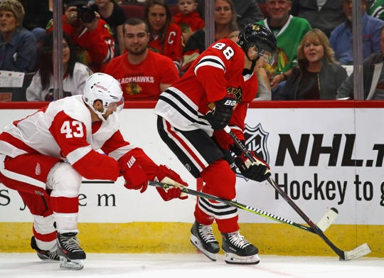 Patrick Kane # 88 The Chicago Blackhawks controls the puck under pressure from Darren Helm # 43 of the Detroit Red Wings during a preseason game at United Center on September 25, 2018 in Chicago, Ill.