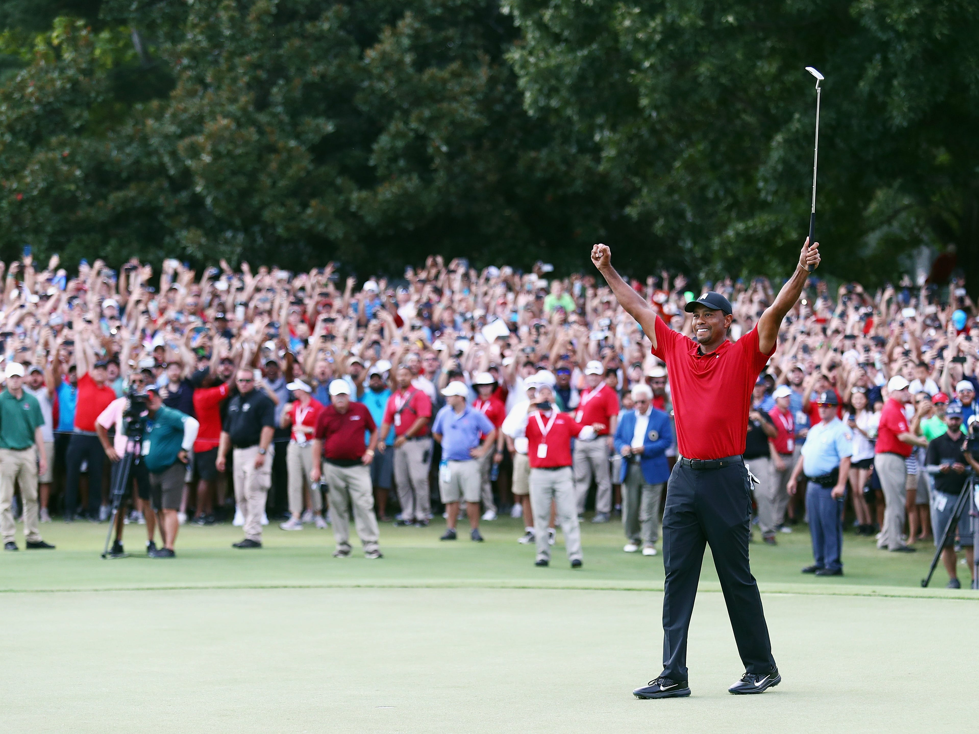 Tiger Woods celebrates making a par on the 18th green to win the TOUR Championship at East Lake Golf Club on September 23, 2018 in Atlanta, Georgia.
