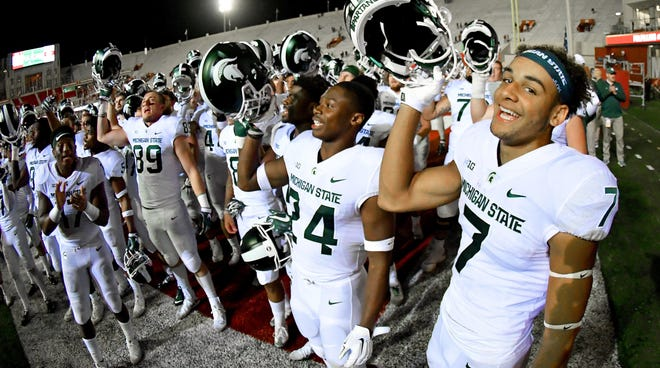 Spartans receiver Cody White, right, celebrates with his teammates after a 35-21 victory over Indiana.