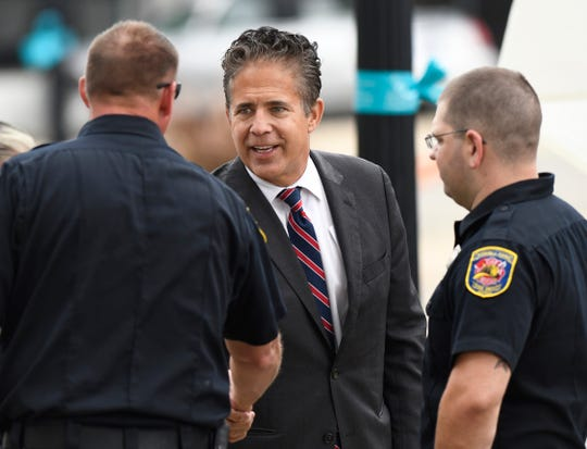 U.S. Rep. Mike Bishop, middle, meets members of the Howell Fire Department before the start of the POW/MIA Recognition Ceremony, Friday, Sept. 21, 2018, at the Livingston County Courthouse in Howell, Mich.