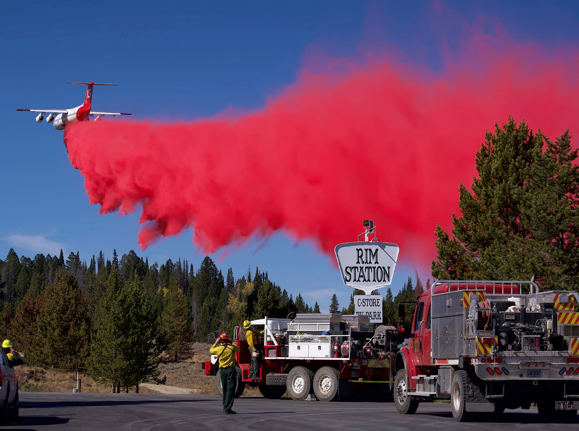 A plane drops fire retardant near the Rim Station, a convenience store and RV park between Bondurant and Daniel, Wyo., on Tuesday, Sept. 25, 2018, during efforts to keep the Roosevelt Fire at bay. The area was evacuated Sunday as the fire approached.