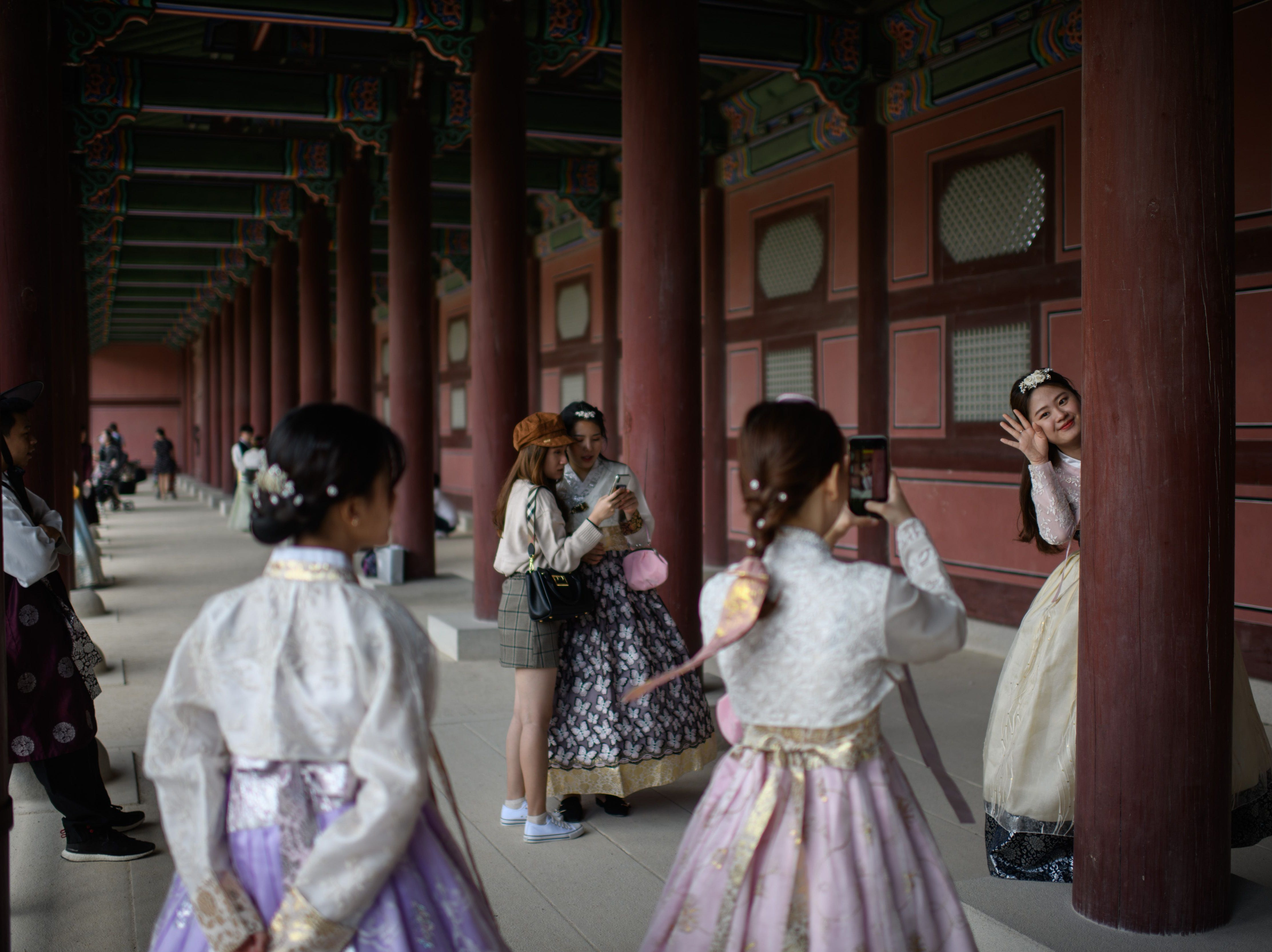 Visitors wearing traditional Korean Hanbok dresses pose for photos at the Gyeongbokgung palace in Seoul on Sept. 26, 2018. South Korea is observing the final day of the annual 'Chuseok' thanksgiving holiday.