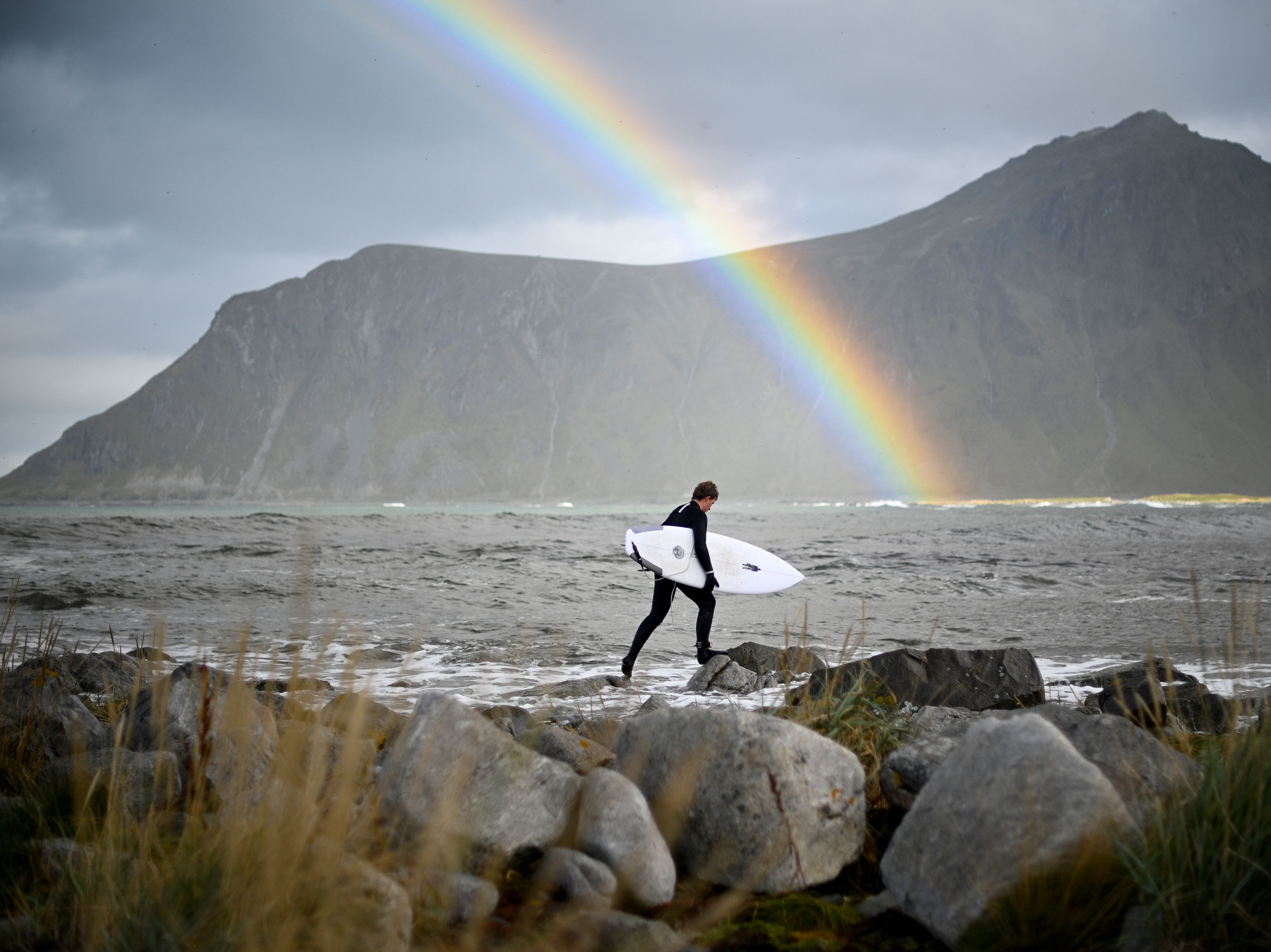 Surfer Anker Olsen Frantzen, 17, of Norway heads out for a free surf session on Sept. 26, 2018,  in Flackstad, Northern Norway, on the eve of the Lofoten Masters 2018. The most-northern surf contest will be held from Sept. 27-30, in Unstad, within the Arctic circle.